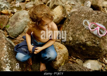 Small child sits on river rock in nature next to a pink pair of goggles, shot from above, Paluma Range National Park, Rollingstone QLD, Australia - Stock Photo