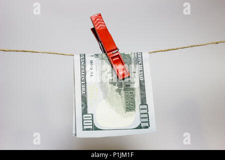 a banknote of one hundred dollars on a laundry rope - Stock Photo