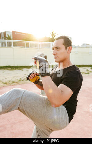 Image of young concentrated strong sports man boxer outdoors make exercises in gloves. - Stock Photo