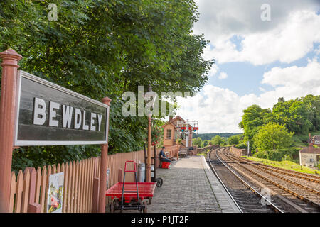 Bewdley vintage railway station, sunlit platform & signal box late afternoon looking up track. Lonely figure sits on trackside bench waiting for train. - Stock Photo