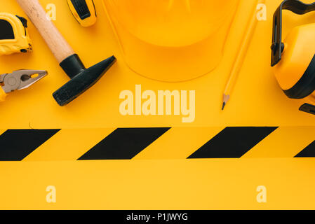 Under construction concept with yellow protective helmet and tools, top view flat lay minimalistic composition - Stock Photo