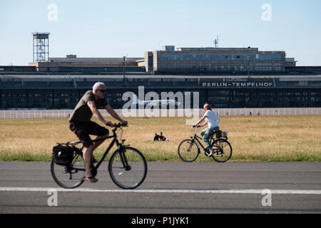 Cyclists on runway at former Tempelhof Airport now public park  in Kreuzberg, Berlin, Germany - Stock Photo