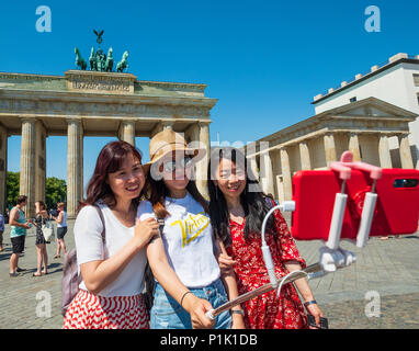 Female Chinese tourists posing with selfie stick in front of Brandenburg Gate in Berlin, Germany - Stock Photo