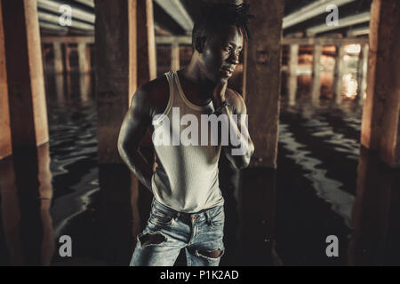 Young African man in white tank top and jeans stands in water under bridge on background of concrete supports. - Stock Photo
