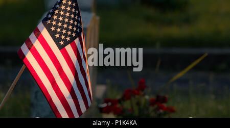 Sun setting on the American Flag in a cemetery - Stock Photo
