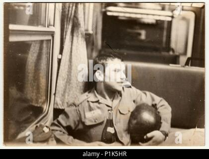 THE CZECHOSLOVAK SOCIALIST REPUBLIC - SEPTEMBER 9, 1981: Vintage photo shows man with bottle of wine sits in railway carriage. Black & white antique photo. - Stock Photo