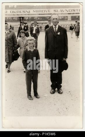 THE CZECHOSLOVAK SOCIALIST REPUBLIC - CIRCA 1960s: Vintage photo shows father and son pose at the socialist celebration. Black & white antique photo. - Stock Photo