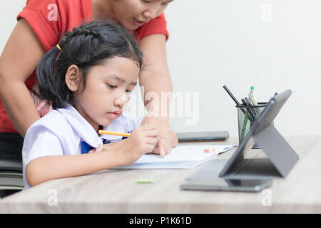 Asian little girl in student uniform doing homework on wooden table with tablet select focus shallow depth of field - Stock Photo