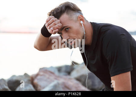 Close up portrait of a exhausted sportsman listening to music with earphones while resting after jogging at the beach