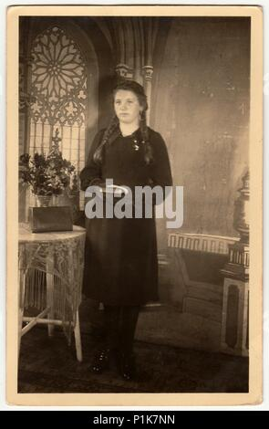 GERMANY - CIRCA 1940s: Vintage photo shows young woman poses with book, she stands next to the table with a bunch of flowers. Black & white antique studio photography with sepia effect. - Stock Photo