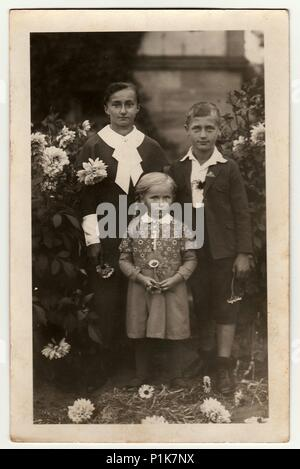 GERMANY - CIRCA 1940s: Vintage photo shows young woman with children (boy and girl) pose in the garden. Black & white antique photography. - Stock Photo