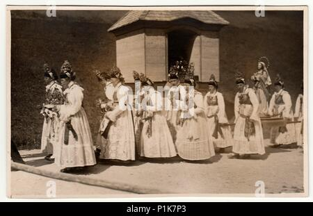 GERMANY - CIRCA 1930s: Vintage photo shows young women during religion procession. Women wear folk costums. Black & white antique photography. - Stock Photo