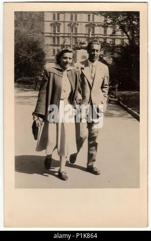 THE CZECHOSLOVAK SOCIALIST REPUBLIC - APRIL 27, 1949: Vintage photo shows a couple goes for a walk in the city park. Black & white antique photo. - Stock Photo