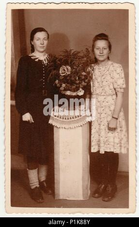 GERMANY - CIRCA 1930s: Vintage photo shows women pose in photo studio with bouquet on a white pedestal. Black & white antique photography. - Stock Photo