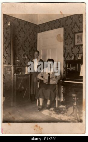 GERMANY - CIRCA 1930s: Vintage photo shows women pose at home. In the picture are piano and stove. Black & white antique photography. - Stock Photo
