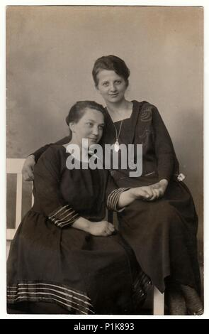 GERMANY - CIRCA 1930s: Vintage photo shows women pose in photo studio. They sit on white historic bench. Black & white antique photography. - Stock Photo
