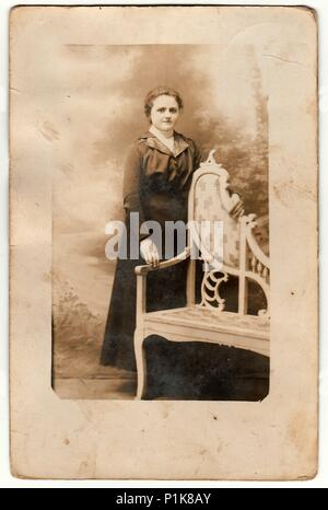 THE CZECHOSLOVAK REPUBLIC - CIRCA 1920s: Vintage photo shows young woman poses next to historic carved bench. Black & white antique photography. - Stock Photo