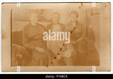 THE CZECHOSLOVAK REPUBLIC - CIRCA 1930s: Vintage photo shows family at home. They sit on the sofa. Antique black & white photography. Note: strong blurriness - Stock Photo