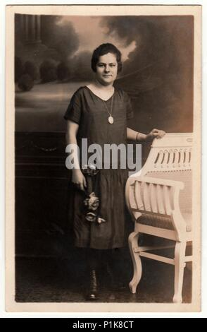 EILENBURG, GERMANY - CIRCA 1930s: Vintage photo shows young woman poses next to historic carved bench. Black & white antique studio photography. - Stock Photo
