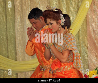 A Buddhist couple, in beautiful wedding clothes, kneel during their wedding ceremony, their hands together in a gesture of prayer and thanks. - Stock Photo