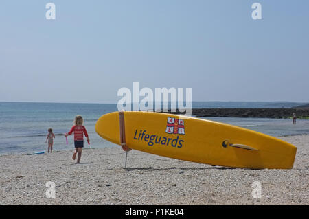 RNLI lifeguards sign on a surfboard - Stock Photo