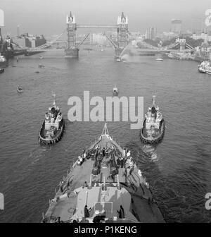 HMS 'Belfast' and Tower Bridge, London, 1971. View looking down onto the foredeck of the cruiser HMS 'Belfast' being guided up the River Thames by two - Stock Photo