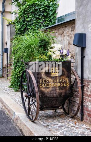 Berlin,Prenzlauer Berg. Restaurant Oderberger sign in old cart serving as  flower planter Outside Hotel Oderberger.Historic building was a former pool - Stock Photo
