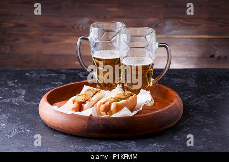 Photo of two mugs of beer and hot dogs on wooden tray - Stock Photo