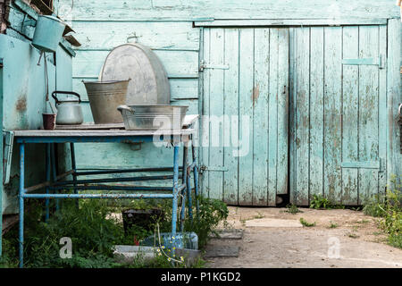 Rural life. Aluminum dishes on the table on the background of the old barn. - Stock Photo