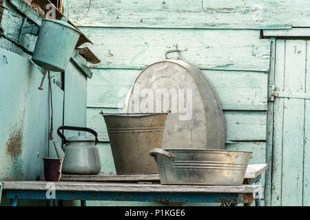 Rural life. Washstand and aluminum utensils on the background of a wooden shed. - Stock Photo