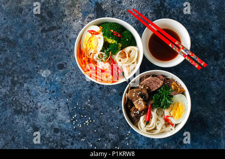 Two variation  udon noodles bowls. with broccoli, ed, carrot, spices and meat, mushrooms, egg and parsley. Top view. - Stock Photo