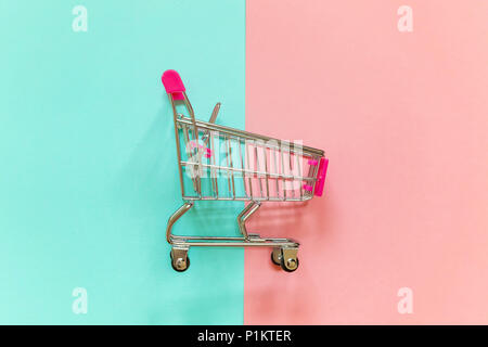 Small supermarket grocery push cart for shopping toy with wheels and pink plastic elements on pink and blue pastel color paper geometric flat lay back - Stock Photo