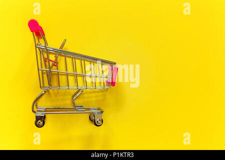 Small supermarket grocery push cart for shopping toy with wheels and pink plastic elements on yellow colourful trendy modern fashion background. Copy  - Stock Photo