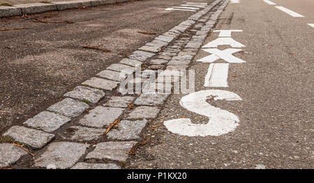 white painted taxi sign on a black asphalt road in France - Stock Photo