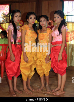 Four beautiful girls at a Cambodian wedding wearing flowers in their hair and dressed in traditional robes wait to play their role in the ceremony. - Stock Photo