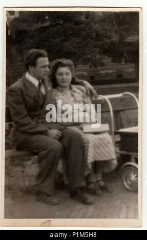 ITALY - CIRCA 1940s: Vintage photo shows a young couple with pram. Couple sits on a bench in the city park. Black & white antique phtography. - Stock Photo