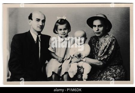 THE CZECHOSLOVAK SOCIALIST REPUBLIC - SEPTEMBER 10, 1947: Retro photo shows Russia family (father, mother and two daughters). Vintage black & white photography. - Stock Photo
