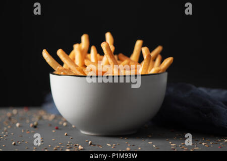 some appetizing french fries served in a white ceramic bowl, placed on a gray rustic wooden table, against a black background - Stock Photo