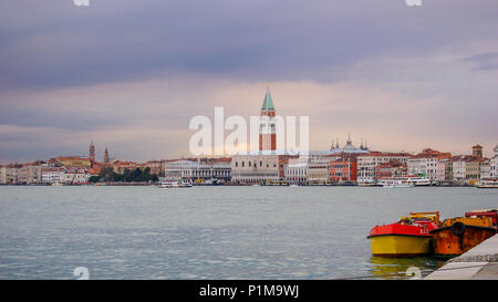 Classic view of St Marks and the Doge Palace across from Giudecca at sunset with spring shower clouds turning the sky violet and purple, Venice, Italy - Stock Photo