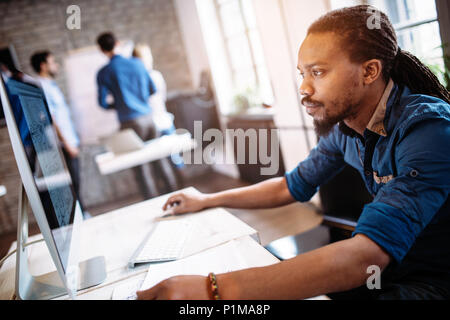 Young architect working on computer in office - Stock Photo