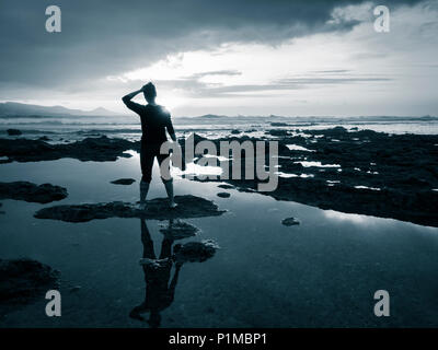 Rear view of woman holding shoes looking out to sea at sunset: meditation, mental health, loneliness, freedom, depression..concept image - Stock Photo