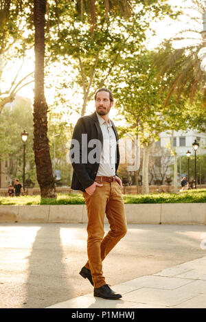 Full length image of unshaved attractive guy 30s with tied hair posing with hands in pockets during walking in green park - Stock Photo