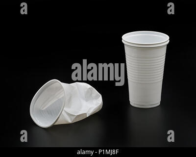 Crushed and new plastic cups isolated on black background. - Stock Photo