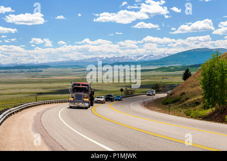 Tractor trailer on highway 285 with South Park valley beyond; from Kenosha Pass; central Colorado; USA - Stock Photo