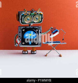 Robotic ironing service concept. Domestic robot housework assistant ironing blue jeans with iron on the board. Red wall, white floor. Copy space - Stock Photo