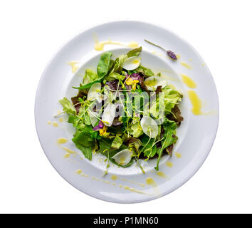 Healthy lettuce arugula salad with edible flowers and microgreens on white plate isolate on white. Top view. - Stock Photo