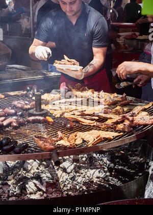 Hispanic cook cooking Sausages, Pork Spare Ribs and others meats cuts on a charcoal bbq in a stall of a Street Food fair. - Stock Photo