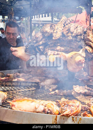 Hispanic cook cooking Pork Spare Ribs and others meats cuts on a charcoal bbq in a stall of a Street Food fair. - Stock Photo