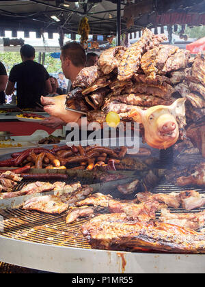 Cook cooking Pork Spare Ribs and others meats cuts on a charcoal bbq in a stall of a Street Food fair. - Stock Photo