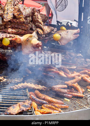 Sausages, Pork Spare Ribs and others meats cuts on a charcoal bbq in a stall of a Street Food fair. - Stock Photo